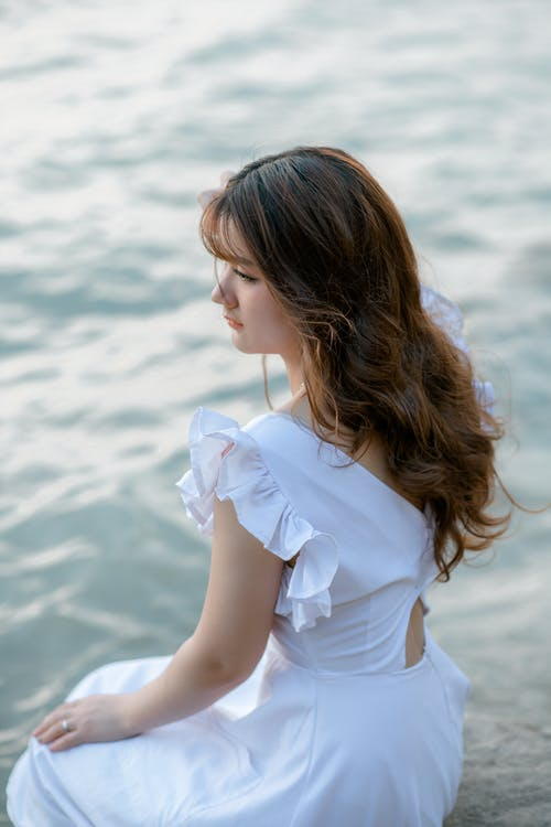 Woman in White Dress Sitting on Rock by the Sea