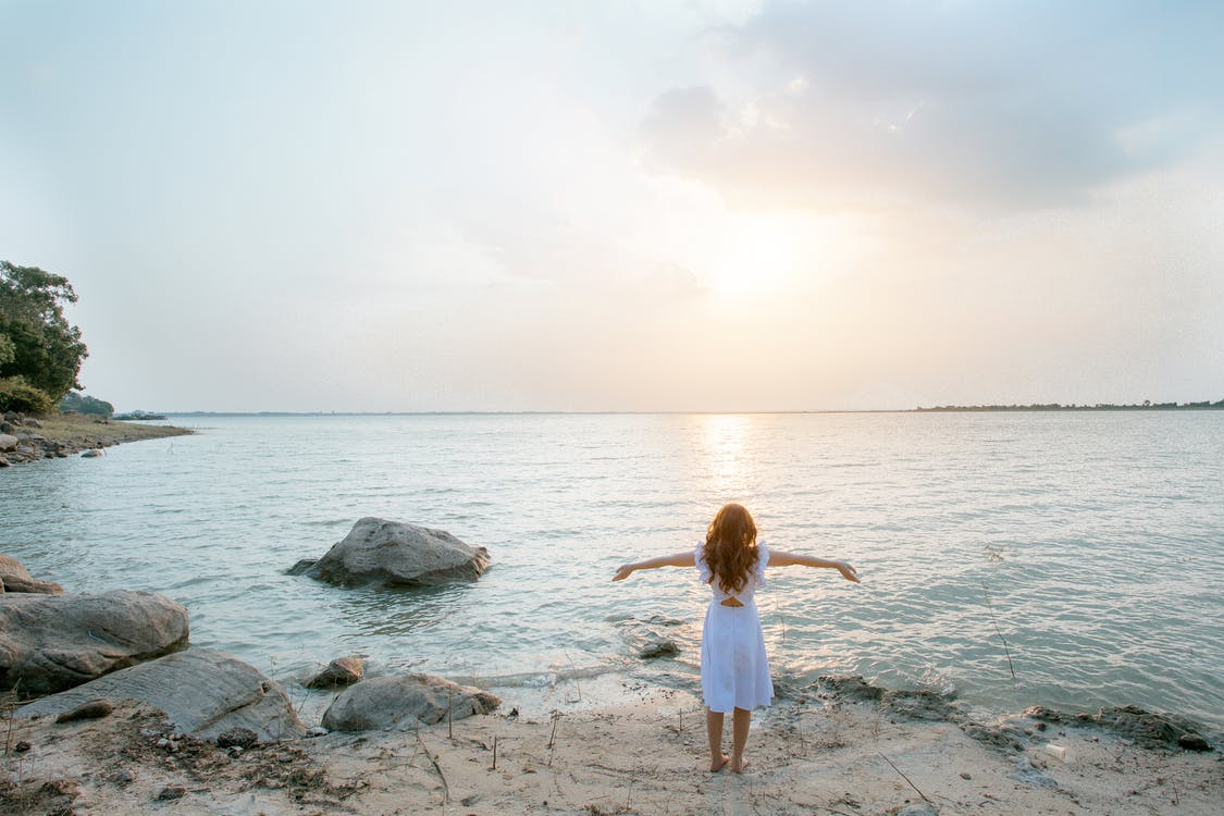 Woman in White Shirt Standing on Gray Rock Near Body of Water