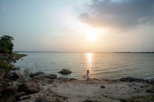 Unrecognizable distant woman standing on sandy coast of rippling sea at sunset in evening