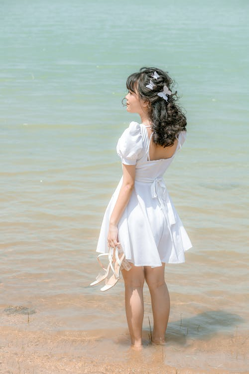 Young bride in white dress standing in water