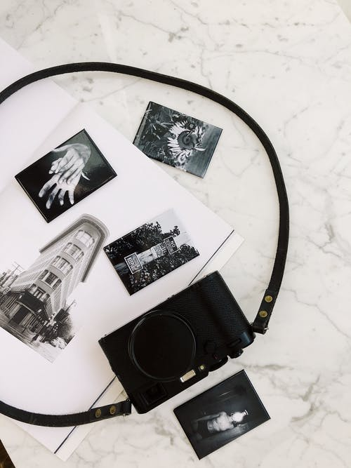 Photo camera placed on white marble surface on album