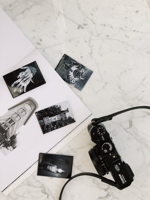 From above of photo camera arranged with black and white photos of album on marble surface