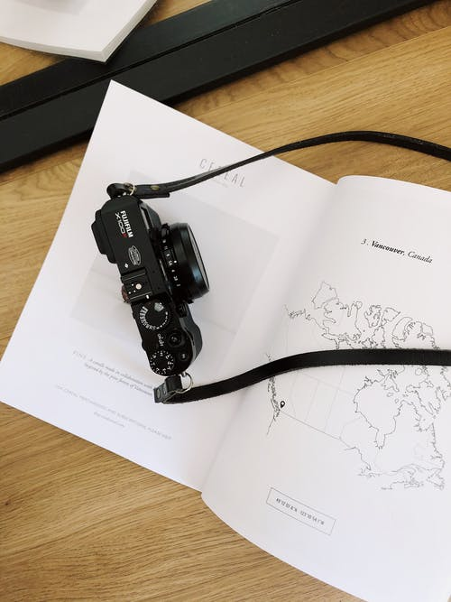 Black photo camera placed on paper book with map on wooden table in modern studio