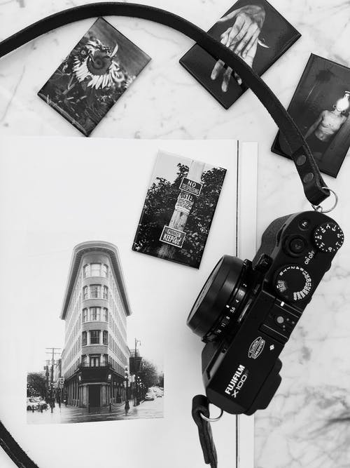Black and white photo camera placed on white marble table near album with various photos in modern studio