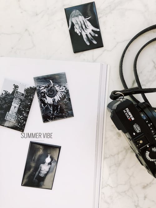 Black photo camera placed on white marble table ner album with various pictures in modern studio
