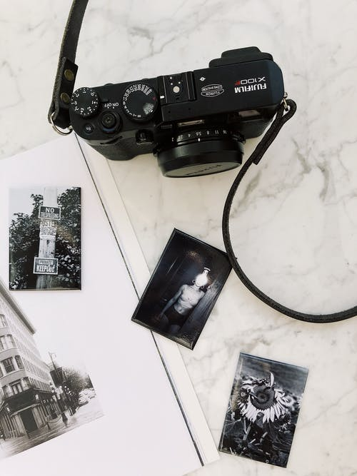 Black photo camera placed on white marble table near album with various pictures in modern studio