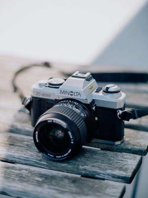 茶色の木製テーブルに黒と銀のニコンデジタル一眼レフカメラ