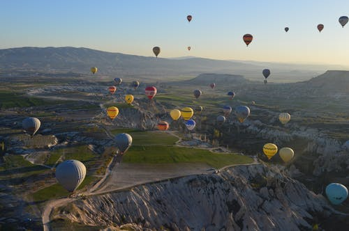 Colorful air balloons flying over highlands during sundown