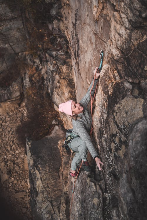 Strong woman climbing up rocky mountain with rope
