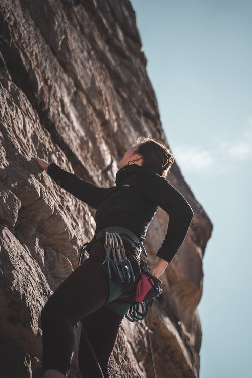 From below side view of unrecognizable female alpinist in sportswear and safety harness gripping boulder and looking up during climbing on rocky formation against cloudless blue sky