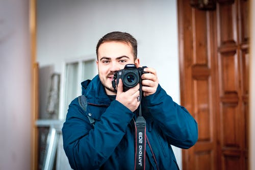Happy young bearded male photographer in warm clothes taking mirror selfie on camera while standing against white studio interior