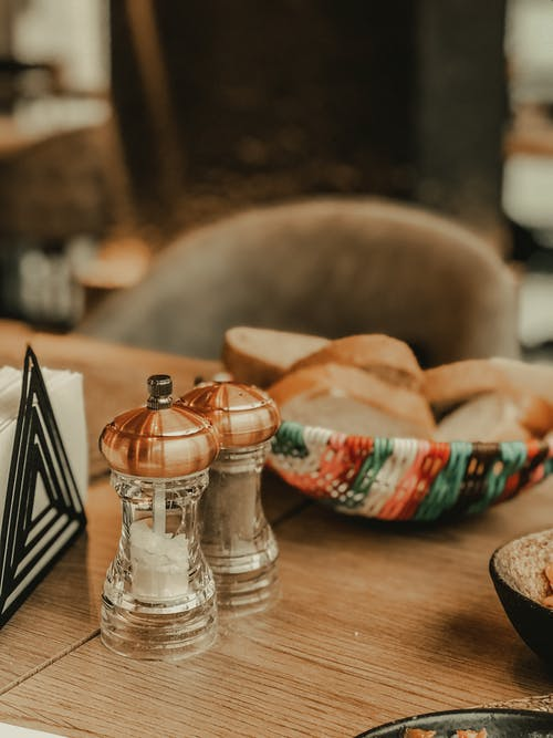 Table served with salt and paper shakers and assorted bread