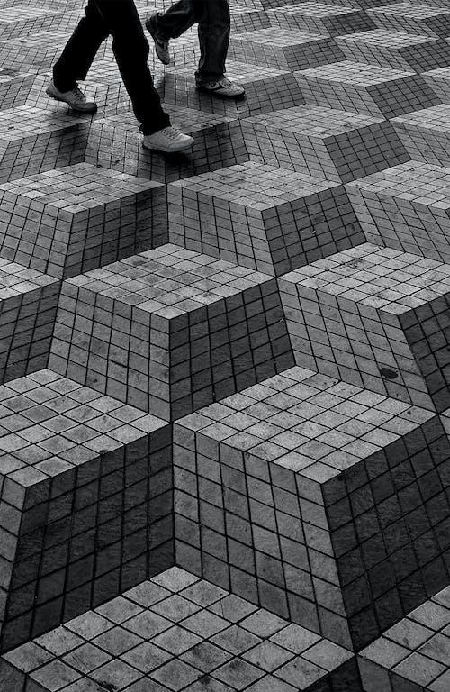 Crop faceless people walking on creative pavement
