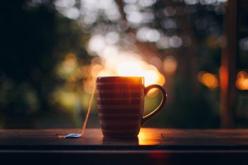 Cup of hot tea on wooden windowsill during sundown