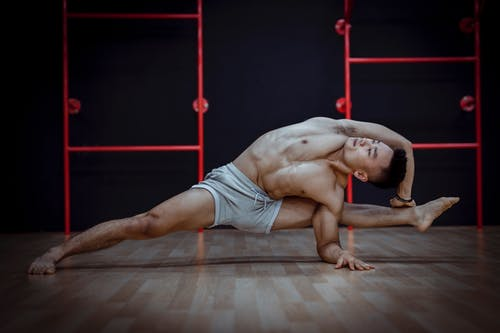 Strong young ethnic man practicing yoga in studio