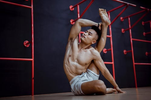 Muscular ethnic instructor doing stretching exercise while practicing yoga