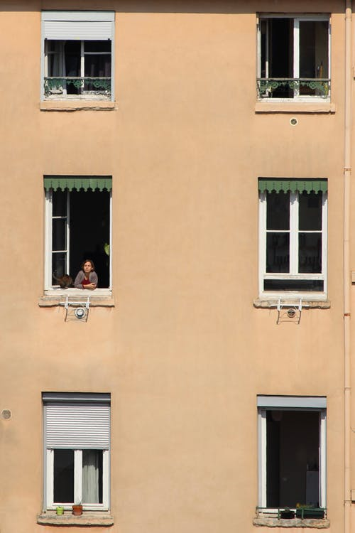 Person On a Window of an Apartment Building