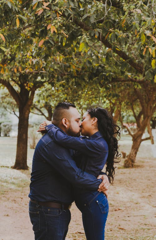 Side view of young ethnic romantic couple in similar outfits embracing and kissing each other during date in autumn park