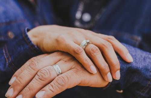 Crop unrecognizable couple holding hands gently
