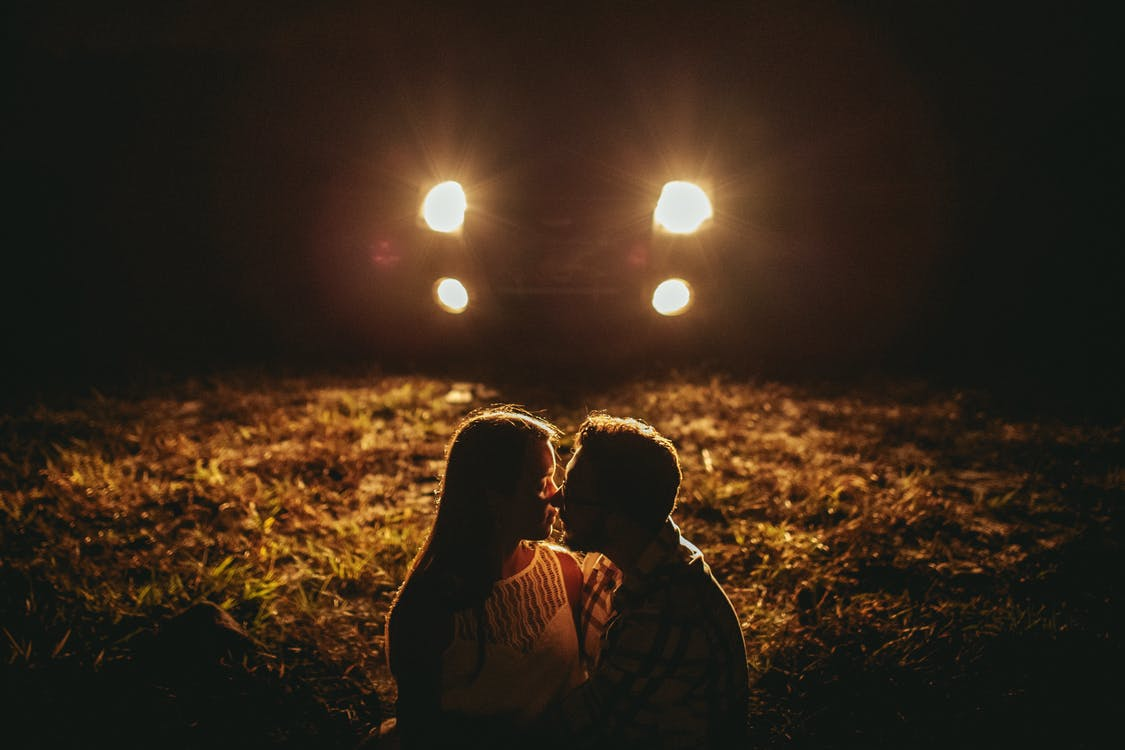Romantic young couple cuddling during date in countryside at night