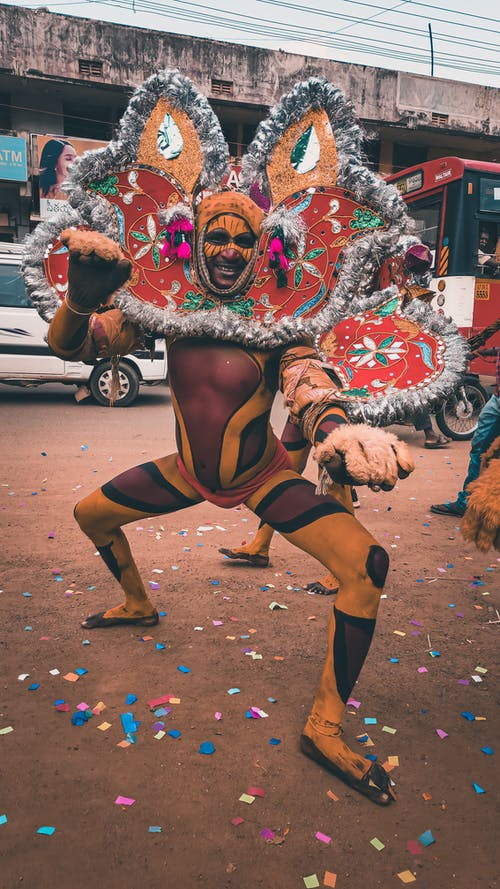 Full body of happy African American barefoot male with body art in bright unusual costume for carnival doing ritual dances on street