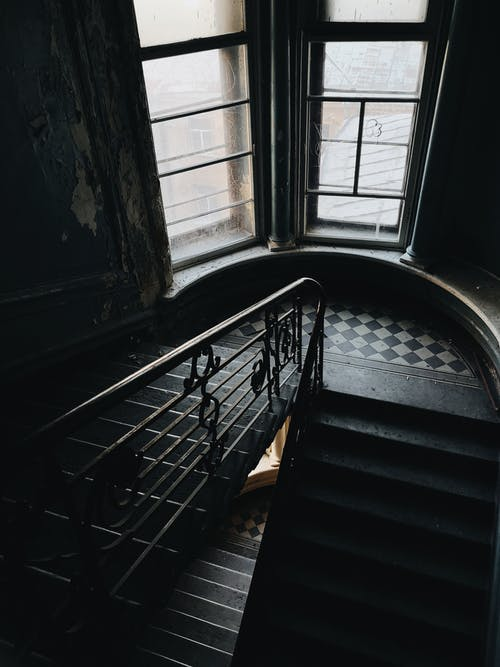 From above of stone stairway and railing in daylight in spacious hall of old building with high ceiling and big narrow windows
