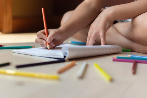 Ground level of unrecognizable kid sitting on floors with legs crossed and drawing in copybook with multicolored pencils