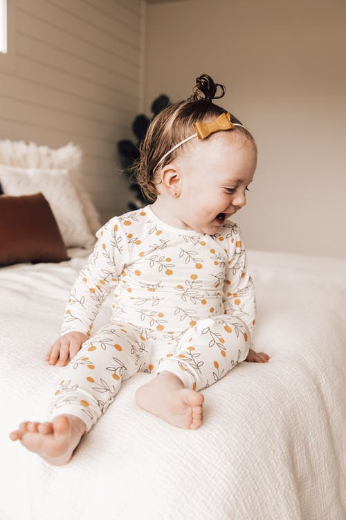 Adorable baby chilling on bed and laughing