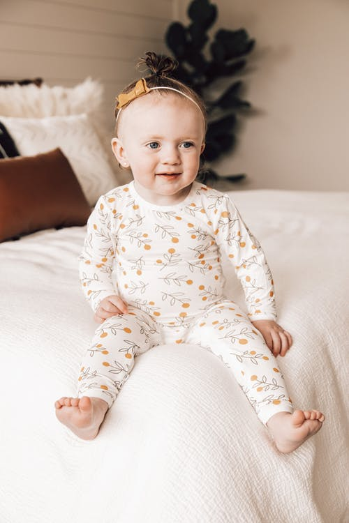 Full body of adorable happy little girl with bow tapped on head in cozy pajama with pattern looking away with warm smile while relaxing on bed