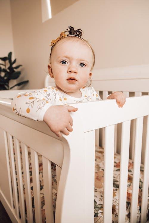 Pensive little girl resting in crib