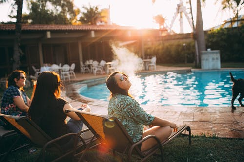 Young woman smoking while resting on poolside