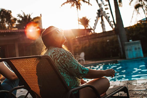 Full body side view of young chubby female traveler in casual clothing smoking and looking away while chilling on sun lounger by swimming pool on sunset
