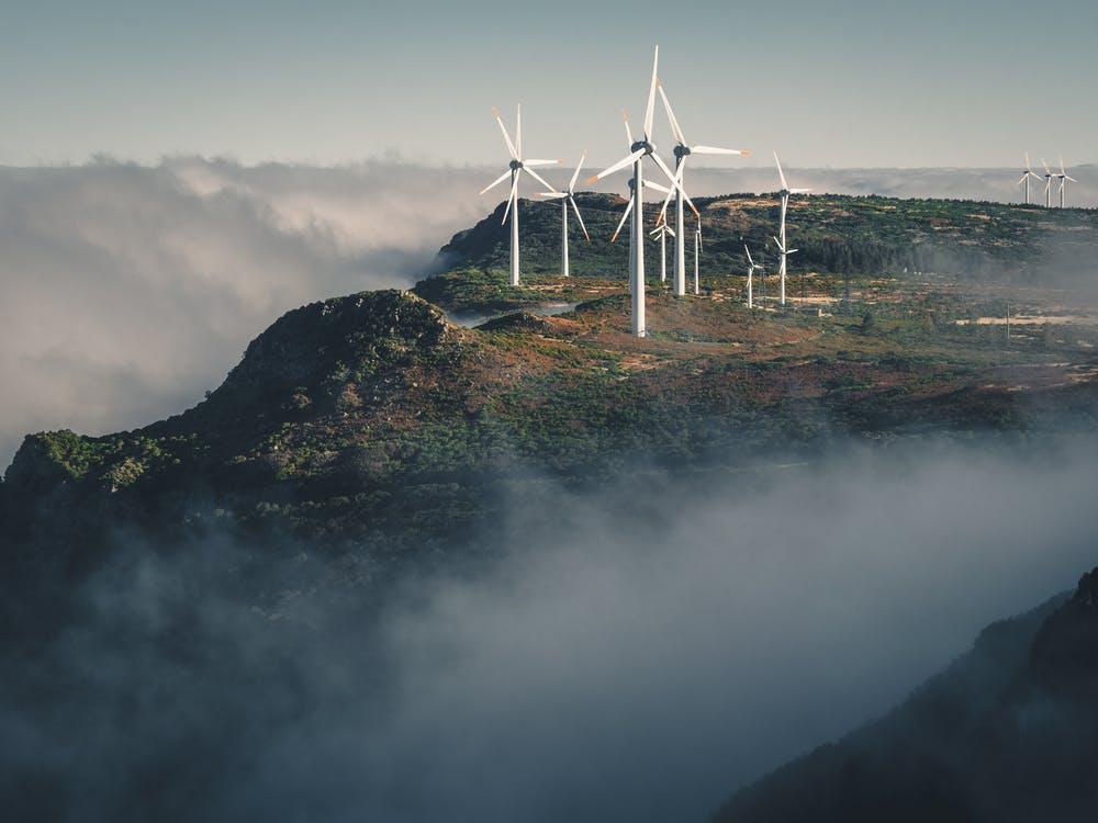 White Wind Turbines on Green Grass Covered Hill