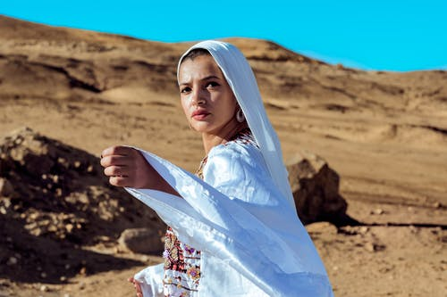 Woman in White Hijab Standing on Brown Sand