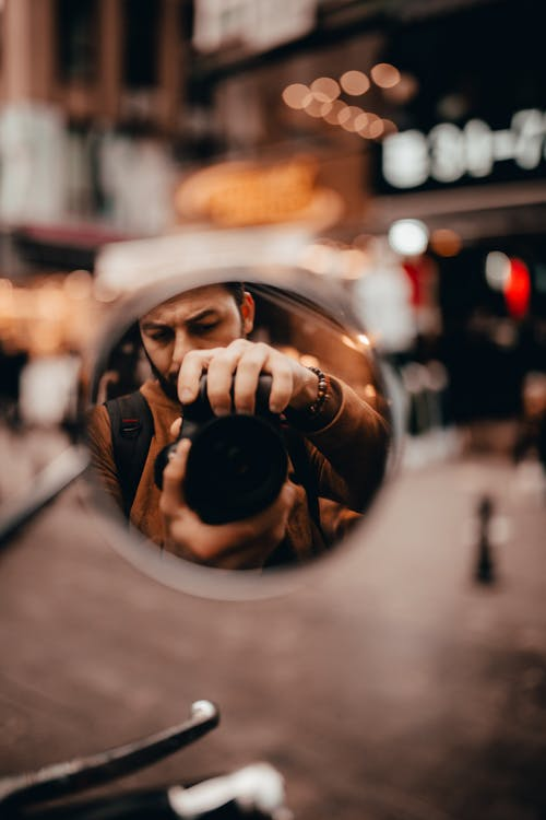 Man Taking Photo on Motorcycle Mirror