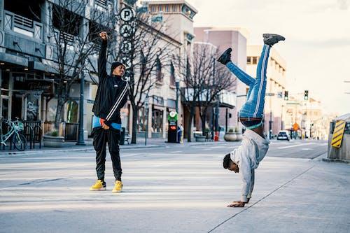 Male friends doing breakdance in center of street