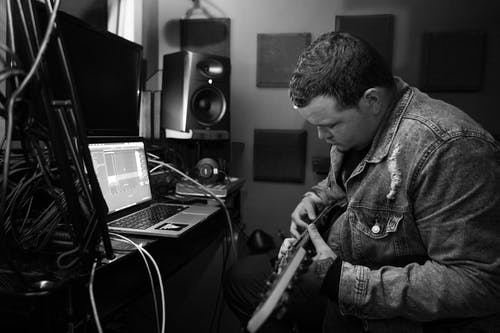 Concentrated musician playing guitar in studio