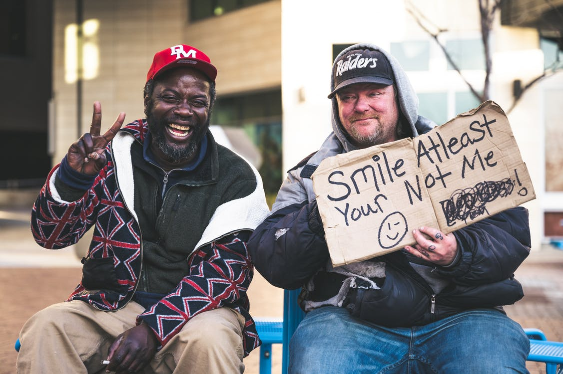 Cheerful African American man in battered clothing showing victory hand with bright smile while male friend holding piece of carton with funny phrase on surface