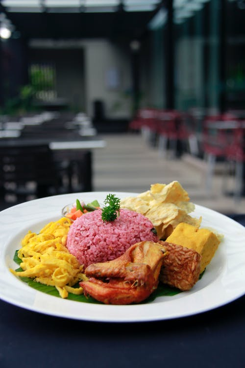 From above of delicious Nasi Ungu dish with rice served on white plate with chicken and various Asian snacks in cafe