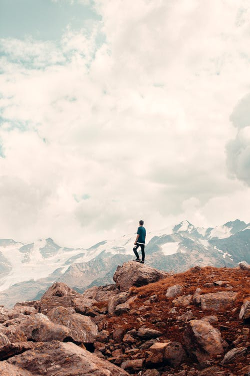 Unrecognizable hiker standing on edge of mountain and admiring view of mountain range under  cloudy sky