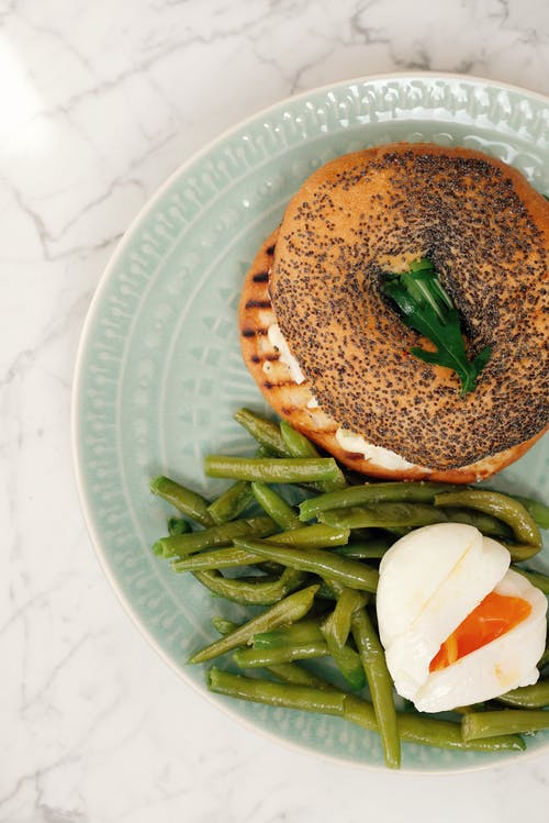 Plate with bagel and asparagus with boiled egg