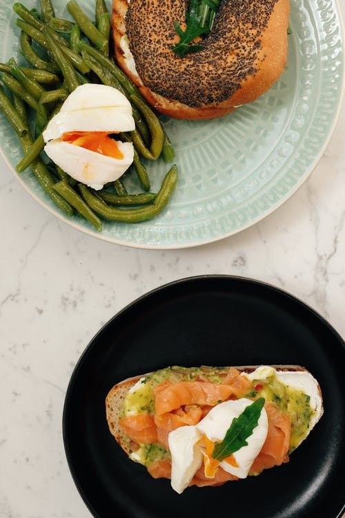From above of served tasty bagel with asparagus and poached egg and fresh toast with avocado and salmon on white marble table
