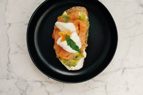 Top view of black ceramic plate with tasty toast with salmon and poached egg served on white marble table