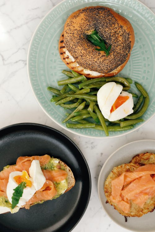 Plates with bagel with asparagus and boiled egg and toasts with fish served on table