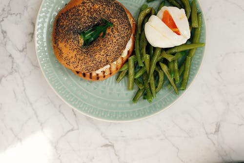 Plate with bagel with asparagus and boiled egg served on table