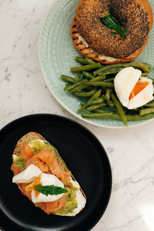 Plates with morning delicious dishes on marble table