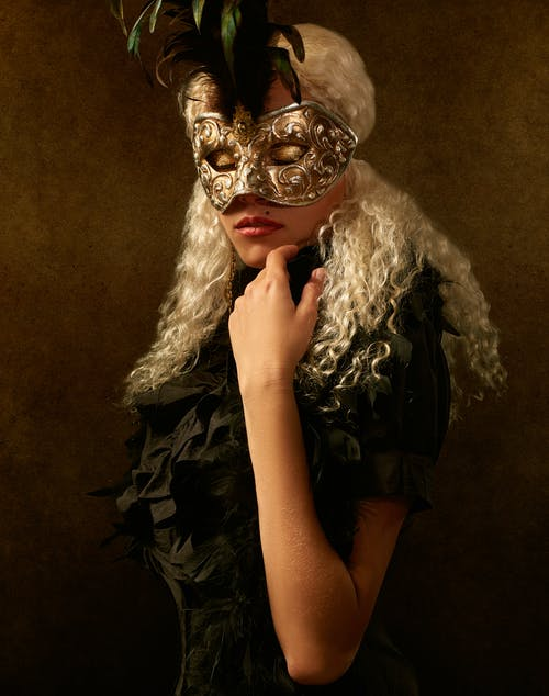 Alluring woman in carnival mask and eyes closed