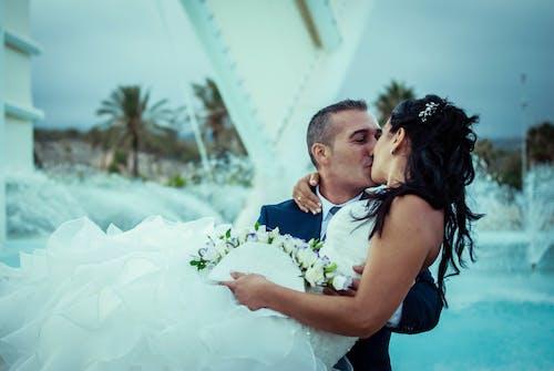 Man in Blue Polo Shirt Kissing Woman in White Wedding Dress