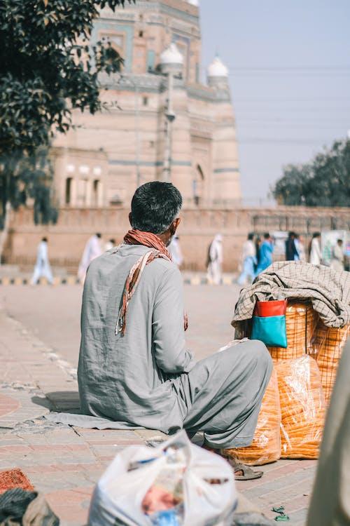 Man in White Long Sleeve Shirt Sitting on Concrete Floor