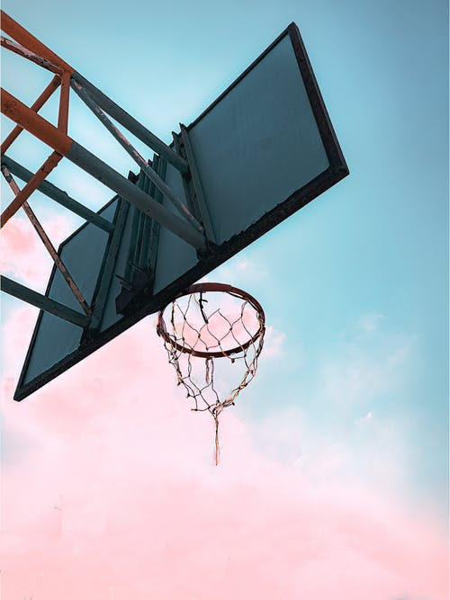 Basketball hoop on sports court against bright sky